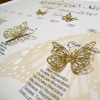 A printed and embellished table plan with glittering laser cut gold butterflies